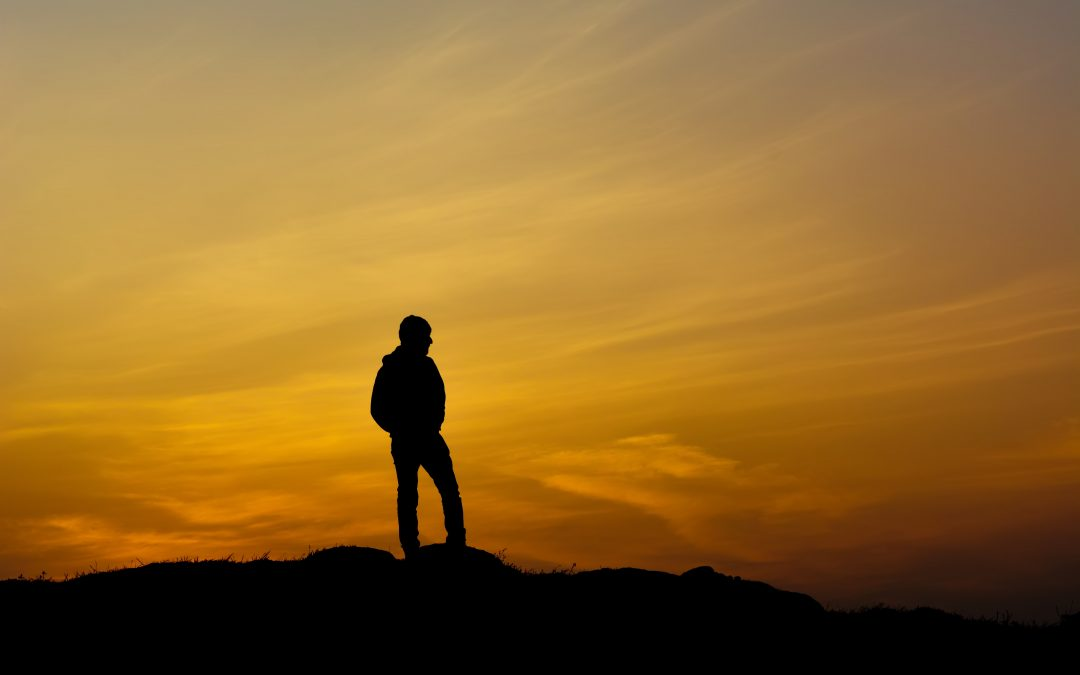 Leader standing alone on during sunset, vulnerable.